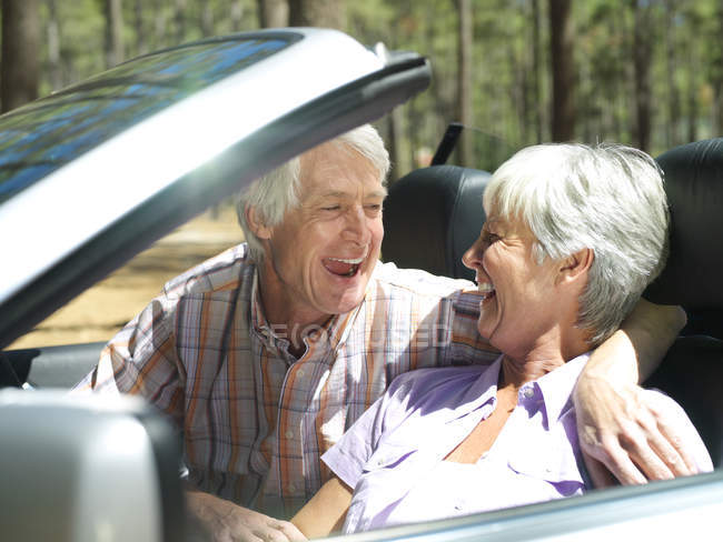 Laughing senior couple sitting in convertible car — Stock Photo