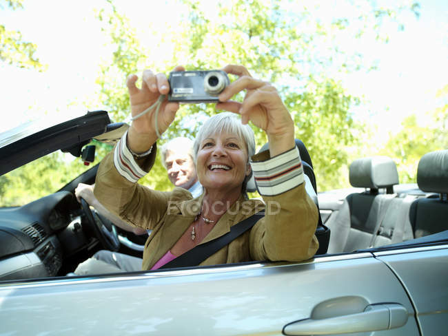 Senior couple driving in convertible car along country road, woman taking photograph — Stock Photo