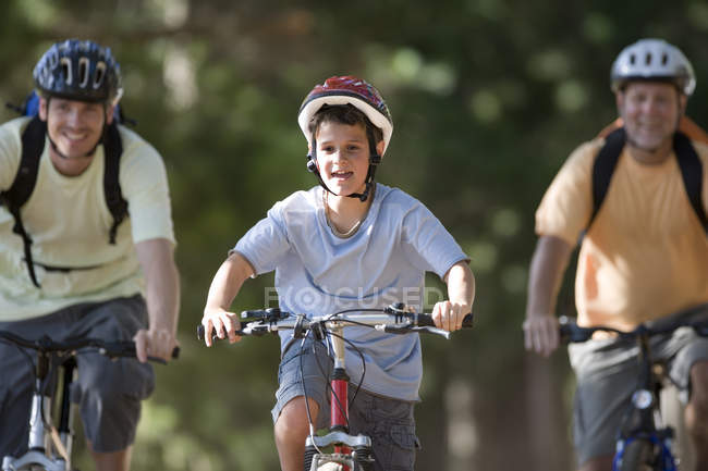 Boy in cycling helmet mountain biking on woodland trail with father and grandfather — Stock Photo