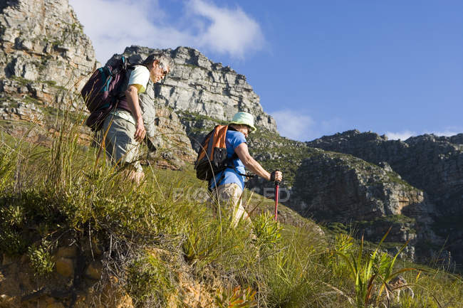 Mature couple hiking on mountain trail, carrying rucksacks — Stock Photo