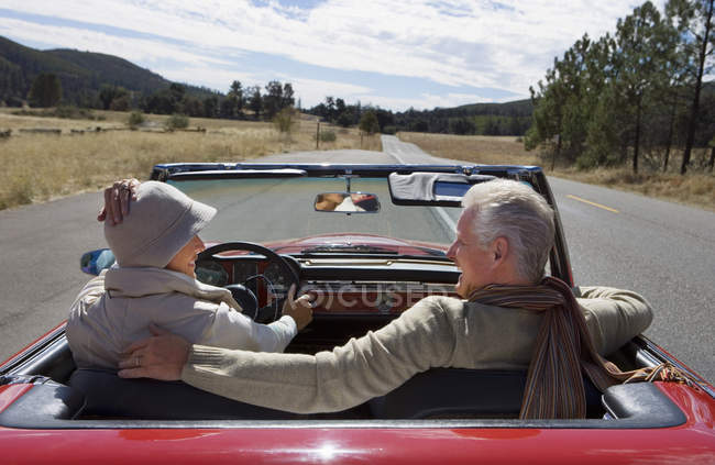 Mature couple sitting in red convertible car on country road — Stock Photo