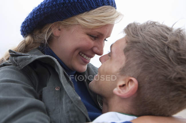 Front view of smiling young couple hugging face to face — Stock Photo