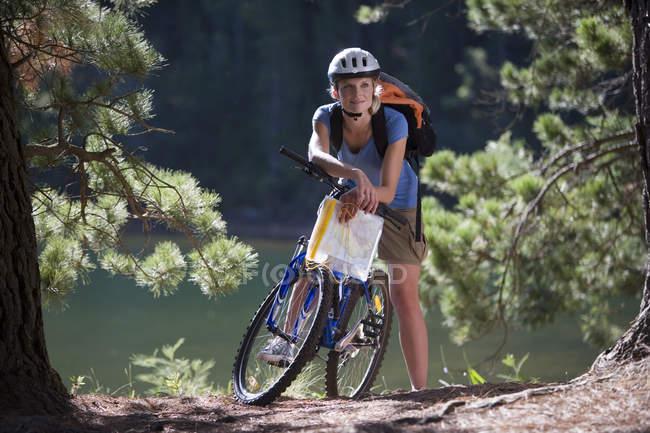 Frau mit Rucksack Mountain biking entlang Waldweg am See und im Besitz Karte — Stockfoto