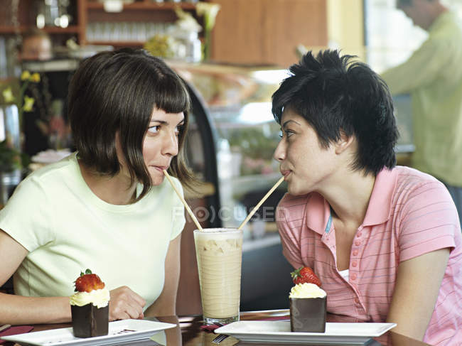 Two young women sitting at cafe table, sharing milkshake and drinking through straws — Stockfoto