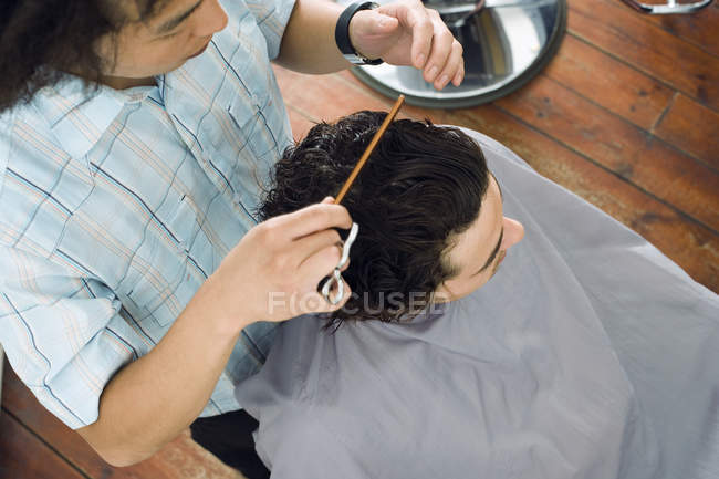 Overhead view of hairdresser combing man hair in barber shop — Stock Photo