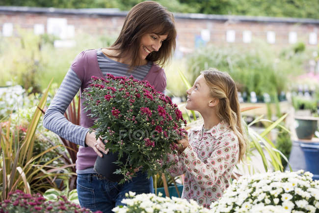 Smiling girl and woman which holding pot with flowers — Stock Photo