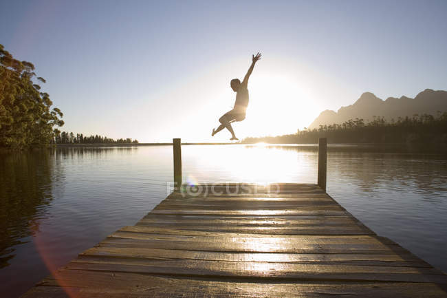Rear view of man jumping from jetty into lake at sunset, lens flare — Stock Photo