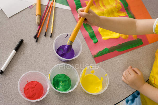 Girl painting on piece of card at desk in classroom, elevated view — Stock Photo