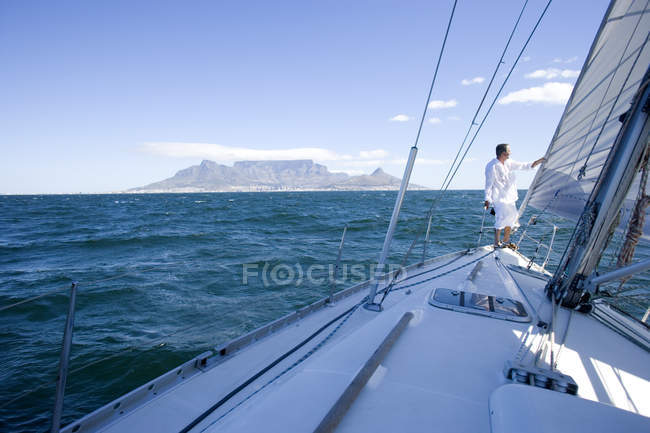 Man standing at bow of yacht out at sea — Stock Photo