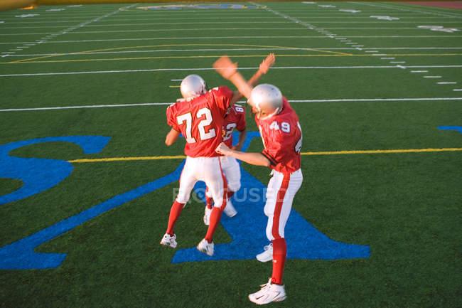 Три американских футболистов в красный футбольный полосы празднование приземления на поле во время конкурентные игры — стоковое фото