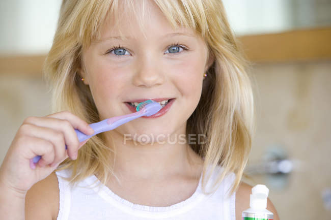 Portrait of girl brushing teeth in bathroom — Stock Photo