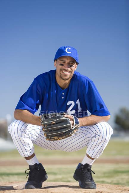 Joueur de baseball portant bleu gant uniforme, protection et cap, accroupie sur terrain — Photo de stock