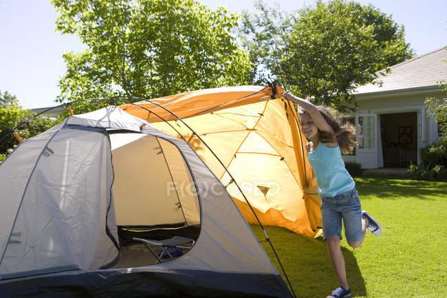 Energisches Mädchen Montage Kuppelzelt auf Wiese im Garten, äußere orange Leinwand über Zelt positionieren — Stockfoto