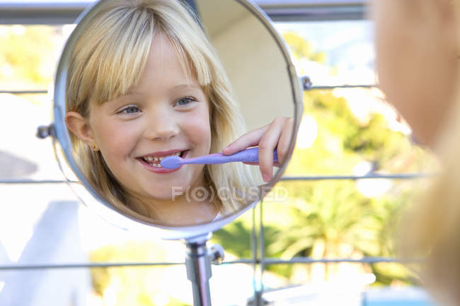 Girl brushing teeth in bathroom and looking at reflection in mirror — Stock Photo