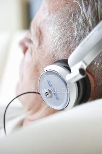 Старший людини, відпочиваючи на диван вдома, прослуховування музики на навушники — стокове фото