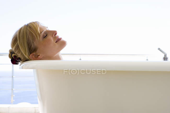 Side view of woman with closed eyes lying in bath — Stock Photo