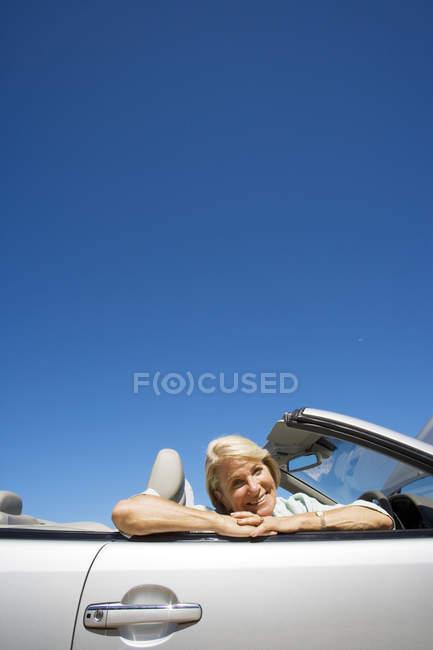 Низький кут зору старший жінка, що сидить у сидіння пасажира Конвертована срібло автомобіля — стокове фото