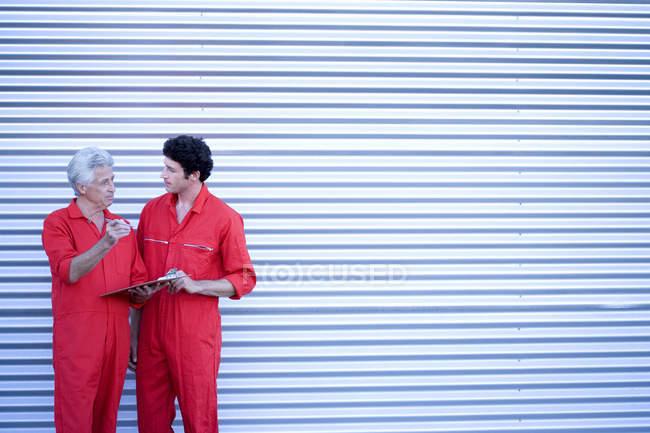Car mechanics standing outside closed rolling garage — Stock Photo