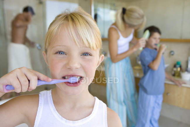 Girl brushing her teeth in bathroom with family members on background — Stock Photo