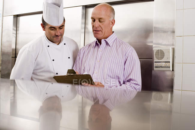 Chef and restaurant manager talking in commercial kitchen — Stock Photo