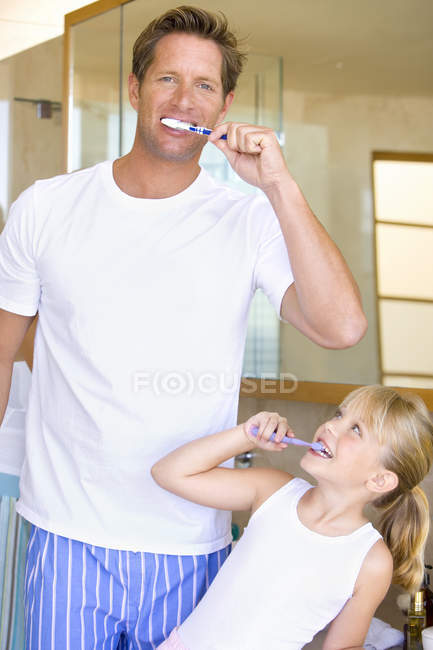 Father and daughter brushing their teeth in bathroom — Stock Photo