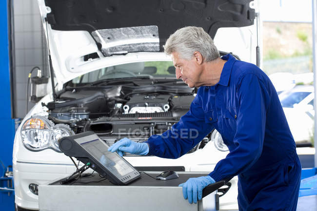 Mature car mechanic using computer — Stock Photo