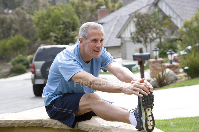 Active senior man in blue t-shirt and shorts stretching legs — Stock Photo