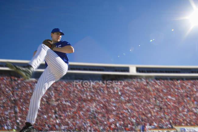 Vue latérale de l'uniforme bleu se préparent à lancer la balle durant le match de compétition de baseball — Photo de stock
