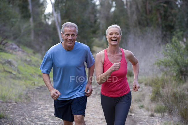 Active senior couple in sportswear jogging side by side along woodland path — Stock Photo