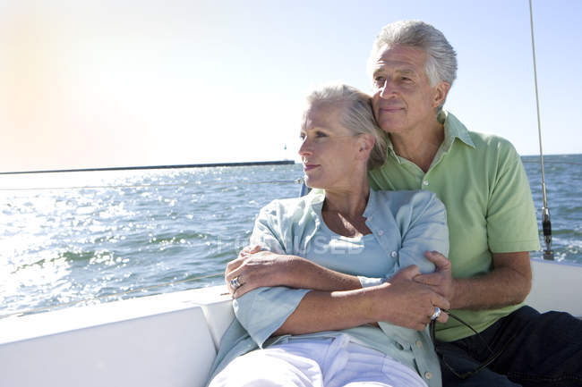 Mature couple sitting on deck of yacht — Stock Photo