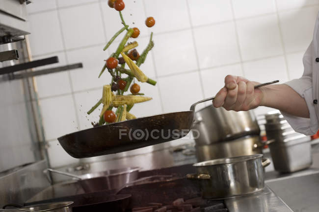 Chef tossing stir fry vegetables in frying pan — Stock Photo