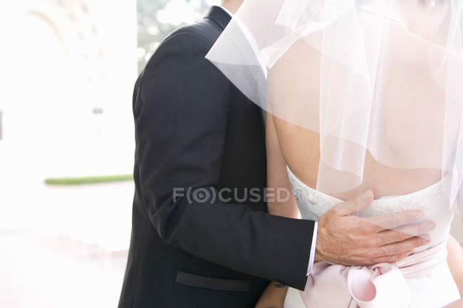 Mid section rear view of groom with arm around brides waist at wedding — Stock Photo