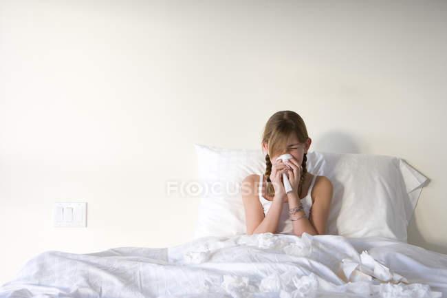 Ragazza seduta dritta nel letto e soffiando il naso con il fazzoletto — Foto stock