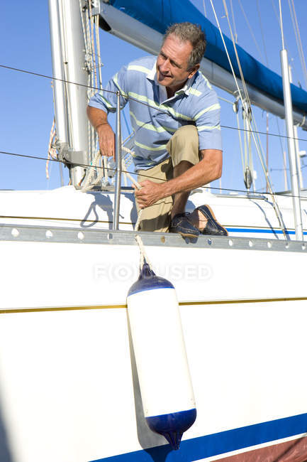 Mature man crouching on deck of yacht — Stock Photo