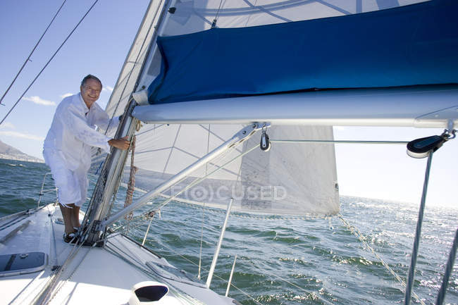 Mature man standing on deck of yacht — Stock Photo