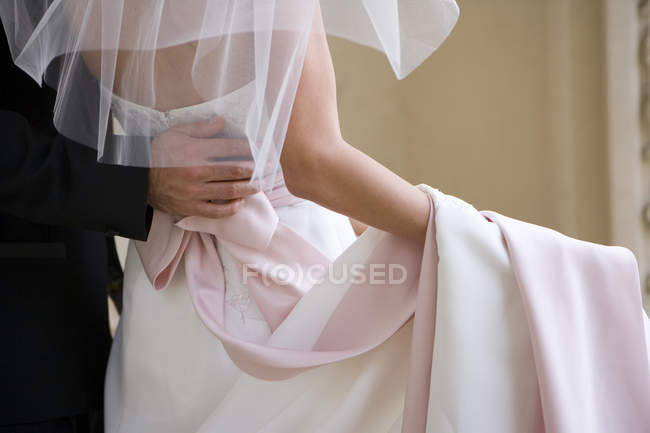 Rear view mid section of groom holding arm around bride at wedding, — Stock Photo