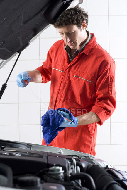 Car mechanic looking at car dipstick — Stock Photo