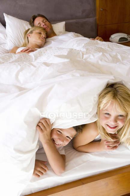 Pareja con hijo e hija tumbada en la cama - foto de stock