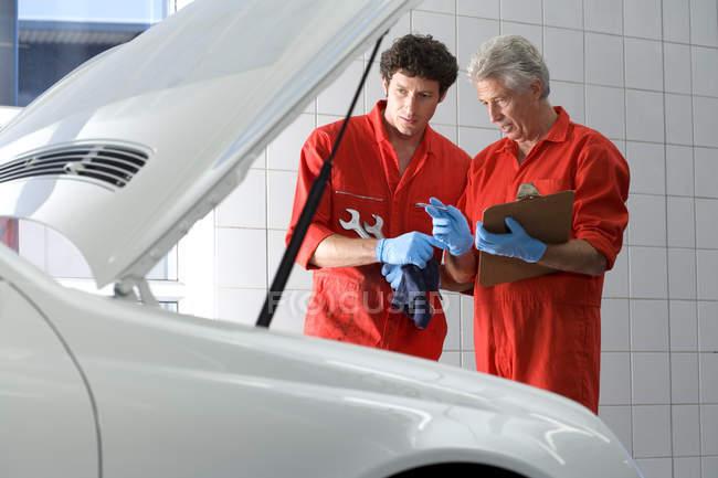 Car mechanics looking at car engine — Stock Photo