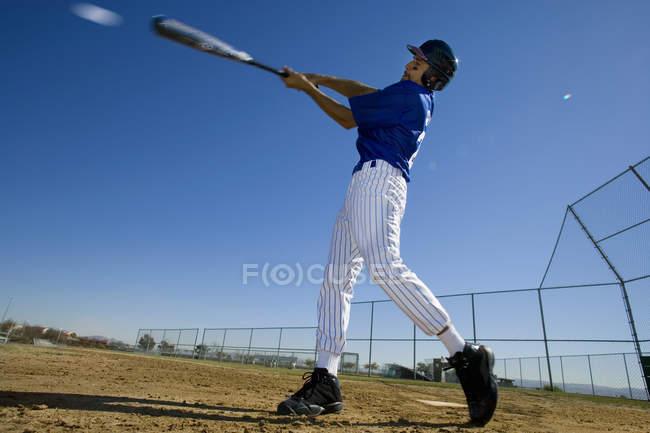 Pâte de base-ball en uniforme bleu, frapper la balle pendant le jeu concurrentiel — Photo de stock