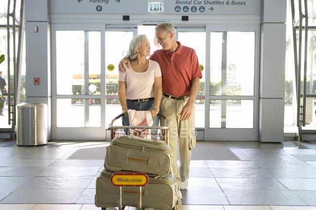 Старший пара введення аеропорту через автоматичні двері, жінка, штовхаючи багажу візок — стокове фото