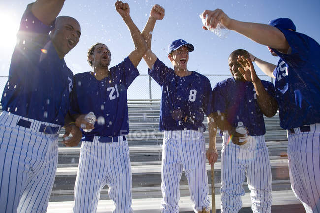Front view of baseball team in blue uniforms standing side by side and celebrating — Stock Photo
