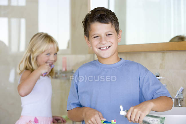 Portrait of brother and sister brushing teeth in bathroom — Stock Photo