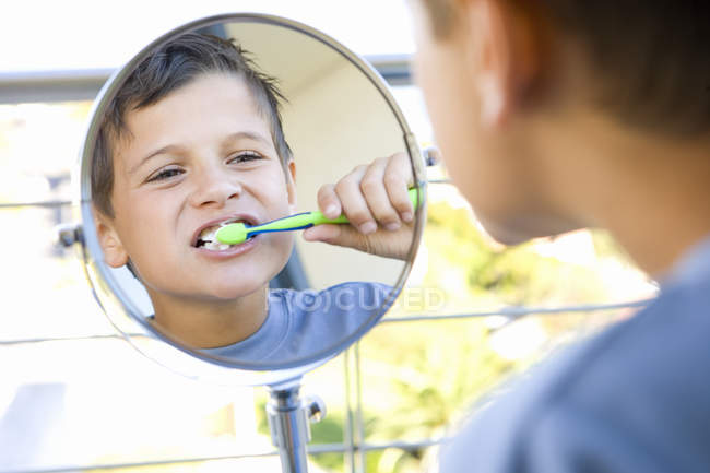 Boy brushing teeth in bathroom and looking at reflection in mirror — Stock Photo