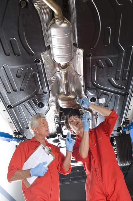 Car mechanics standing below car on hydraulic platform — Stock Photo
