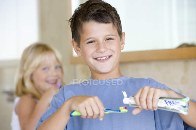 Smiling boy applying toothpaste on toothbrush in bathroom with girl on background — Stock Photo