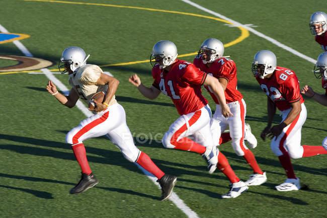 Jugadores de fútbol americano persiguiendo a jugador contrario correr con la bola a velocidad durante el juego - foto de stock
