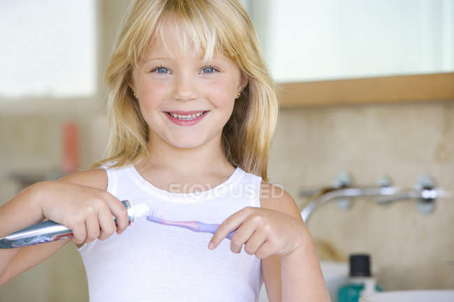 Girl applying toothpaste on brush in bathroom — Stock Photo