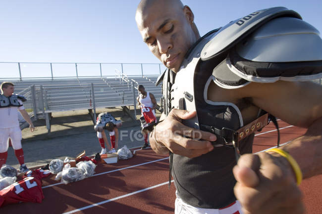 American football player adjusting protective shoulder pad strap pitchside on sports track — Stock Photo