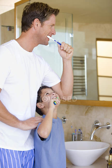 Father and son brushing their teeth in bathroom — Stock Photo